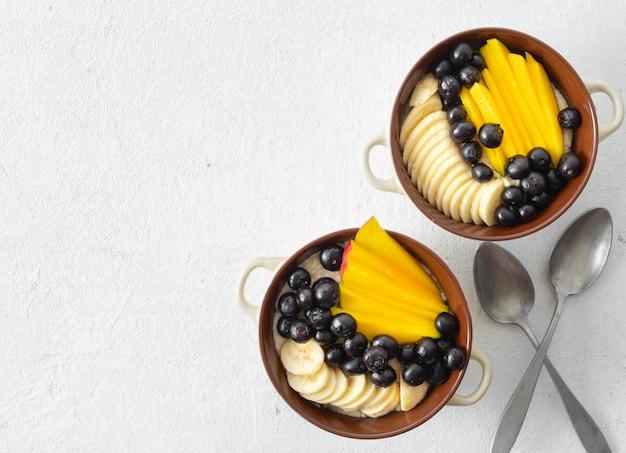 Miska z płatkami owsianymi i mango, jagodami, bananem na białym widoku z góry. widok z góry śniadanie