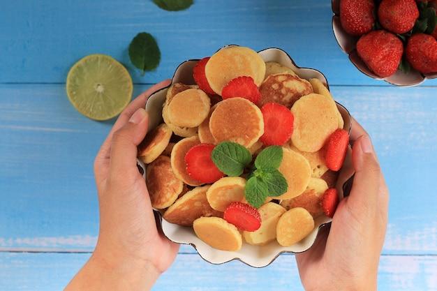 Miska z płatkami tiny pancake z truskawkami, cytryną i listkami mięty na niebieskim tle. modne jedzenie. mini naleśniki zbożowe. orientacja krajobrazowa z małymi dziećmi trzymającymi miskę