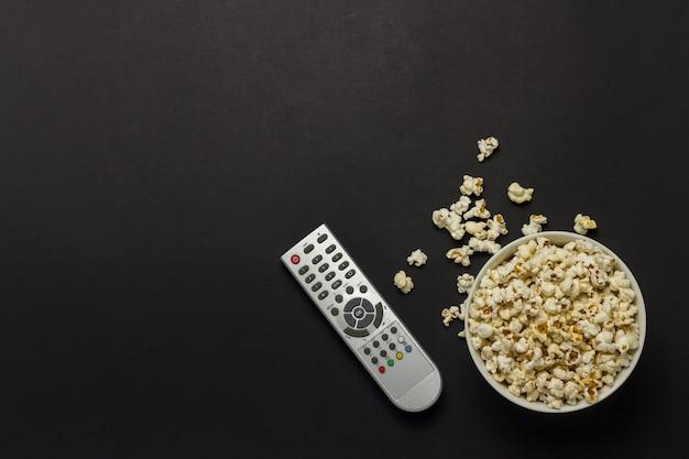 Miska z popcornem i pilotem tv na czarnym tle. koncepcja oglądania telewizji, filmu, seriali, sportu, programów. leżał płasko, widok z góry.