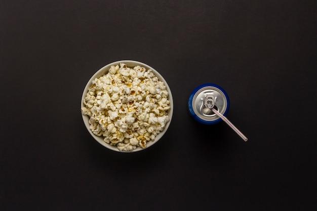 Miska z popcornem i puszka napoju na czarnym tle. koncepcja oglądania filmów i ulubionych programów telewizyjnych, zawodów sportowych. leżał płasko, widok z góry.