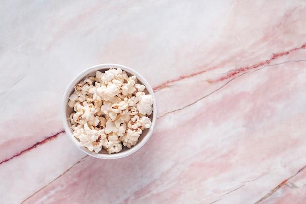 Miska z popcornem na białym i czerwonym marmurze. pokazy, filmy dokumentalne lub filmy gastronomiczne.