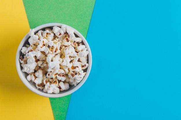 Miska z popcornem na kolorowym tle. gatunki filmów koncepcyjnych. gatunki filmowe: komedia, fantasy, filmy dziecięce i dokumentalne