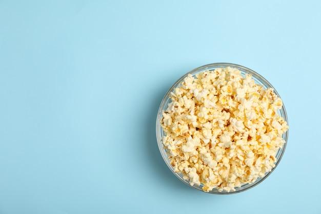 Miska z popcornem na niebiesko. jedzenie do oglądania kina