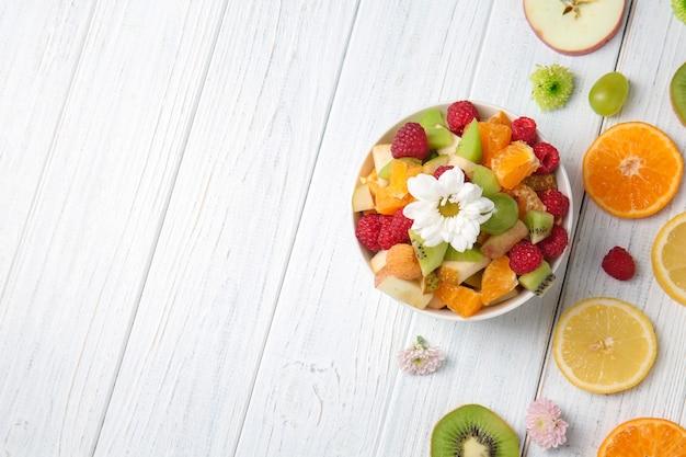 Miska z pyszną sałatką i pokrojonymi owocami na jasnym drewnianym stole