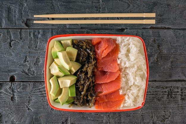Miska z ryżem długoziarnistym, wodorostami, plasterkami awokado, łososiem i drewnianymi paluszkami na ciemnym drewnianym stole. widok z góry.