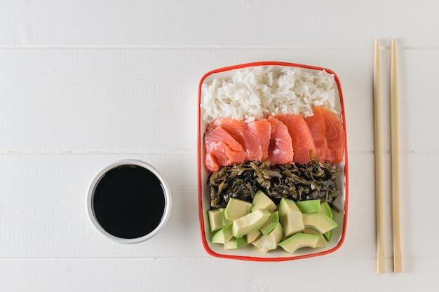 Miska z ryżem długoziarnistym, wodorostami, plastrami awokado, łososiem i drewnianymi pałeczkami na lekkim stole. widok z góry.