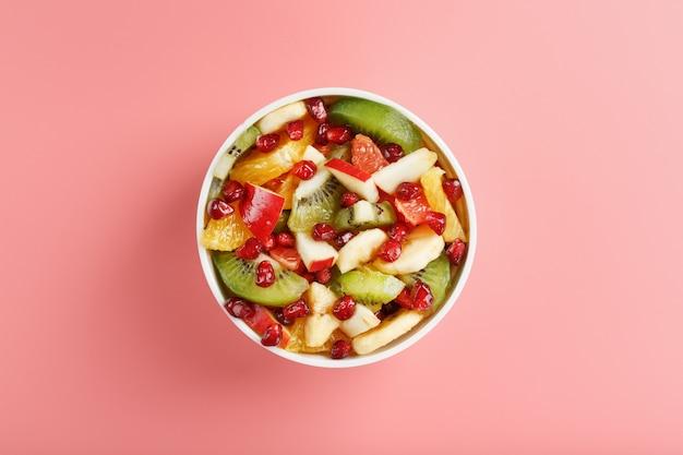 Miska z sałatką owocową na różowym tle. plasterki soczystych i dojrzałych owoców. widok z góry