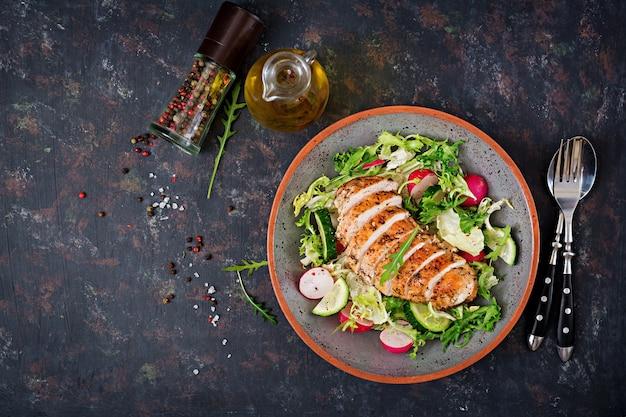 Miska z sałatką ze świeżych warzyw i pieczonej piersi z kurczaka na ciemnym tle. odpowiednie odżywianie. menu dietetyczne. leżał płasko. widok z góry