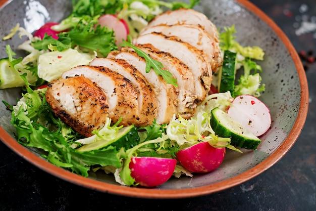 Miska z sałatką ze świeżych warzyw i pieczonej piersi z kurczaka na ciemnym tle. odpowiednie odżywianie. menu dietetyczne.