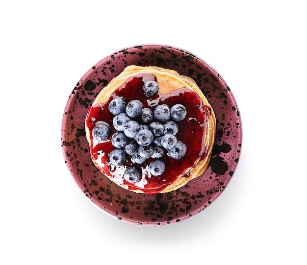 Miska z smacznymi naleśnikami, dżemem i jagodami na białym tle