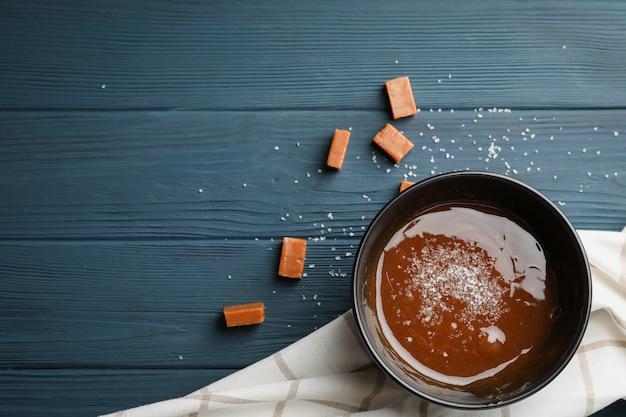 Miska z solonym karmelem i cukierki na drewnianej przestrzeni, miejsca na tekst