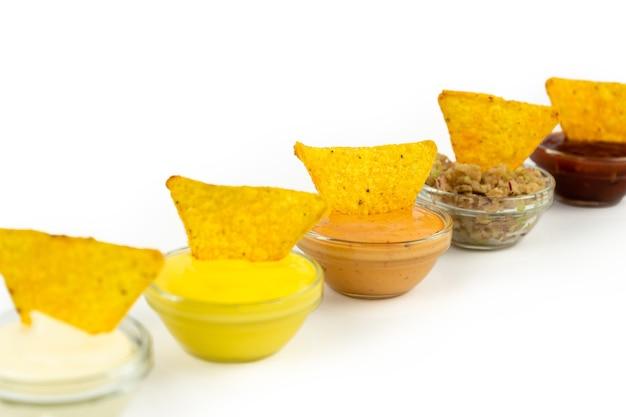 Miska z sosem na białym talerzu z chipsami kukurydzianymi nachos. izolacja na białym tle.