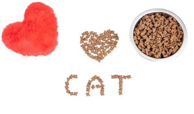 Miska z suchą karmą dla zwierząt domowych i zabawką z czerwonym sercem na białym tle. z miłości do koncepcji zwierząt i walentynek. widok z góry. skopiuj miejsce.