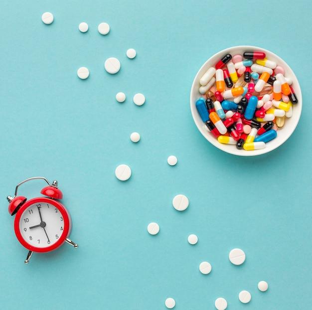 Miska z tabletkami i zegarem obok