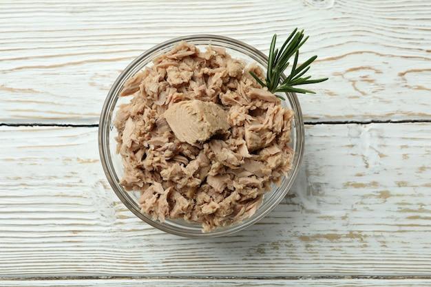 Miska z tuńczykiem w puszkach na białym drewnianym tle