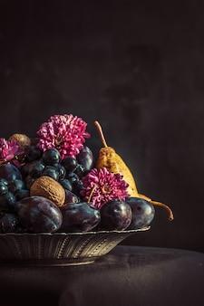 Miska z winogronami i śliwkami na ciemnej ścianie
