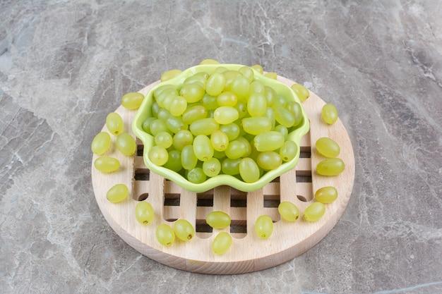 Miska z zielonych winogron na kawałku drewna.