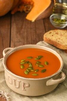 Miska z zupą dyniową podawana z nasionami na worze z dodatkami na podłoże drewniane.