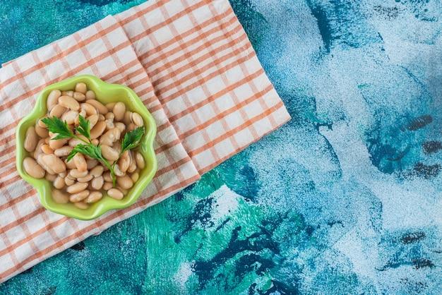 Miska ząbek fasolka po bretońsku na ręcznik, na niebieskim tle.