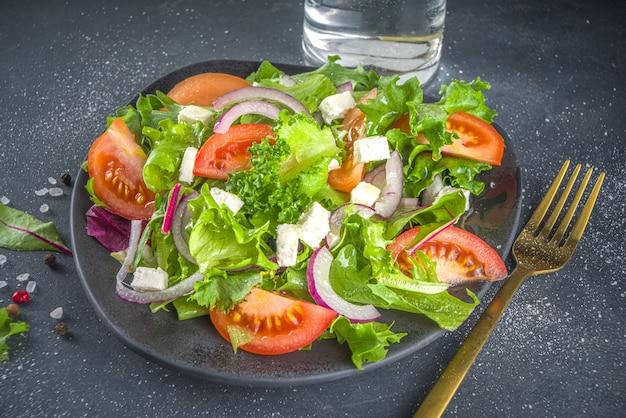 Miska zdrowej sałatki warzywnej z różnymi sałatkami liściastymi, pomidorami, serem feta, cebulą, oliwą z oliwek