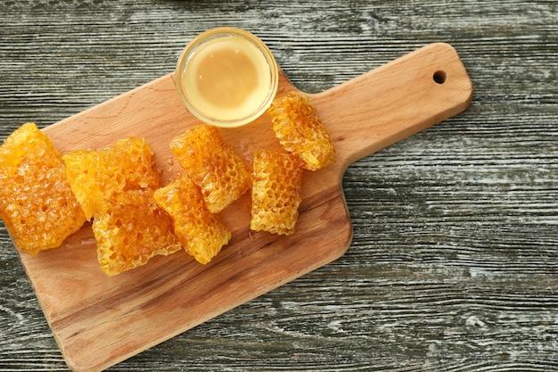 Miska ze słodkim miodem i kawałkami świeżych plastrów na drewnianym stole
