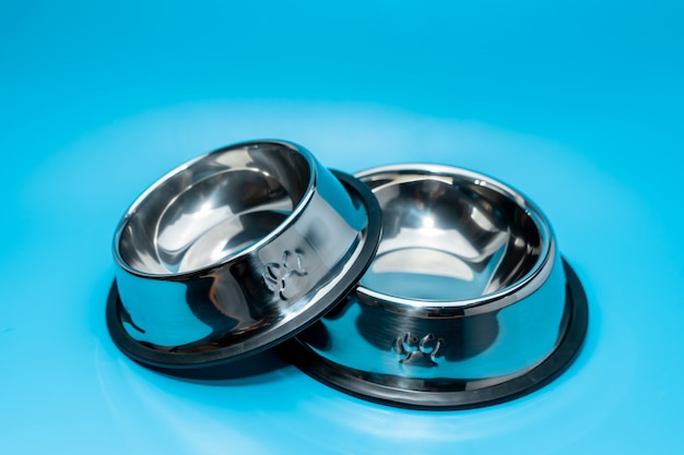 Miska ze stali nierdzewnej na niebieskim tle. koncepcja dostaw dla zwierząt domowych