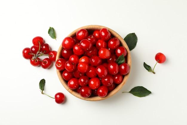 Miska ze świeżych czerwonych wiśni na białym tle