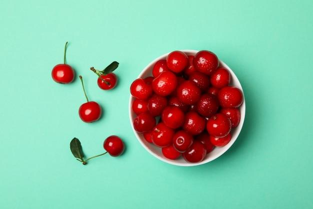 Miska ze świeżych czerwonych wiśni na tle mięty