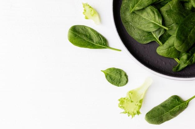 Miska ze świeżych liści sałaty zielonej, szpinaku, sałaty, bazylii na białym tle