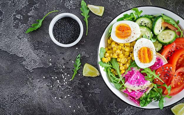 Miska ze świeżymi surowymi warzywami - ogórkiem, pomidorem, rzodkiewką arbuza, sałatą, rukolą, kukurydzą i gotowanym jajkiem