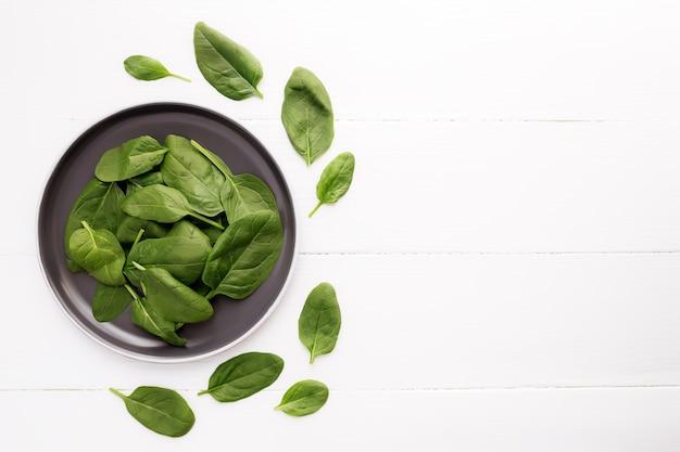 Miska ze świeżymi zielonymi liśćmi szpinaku. koncepcja zdrowego wegetariańskiego jedzenia.
