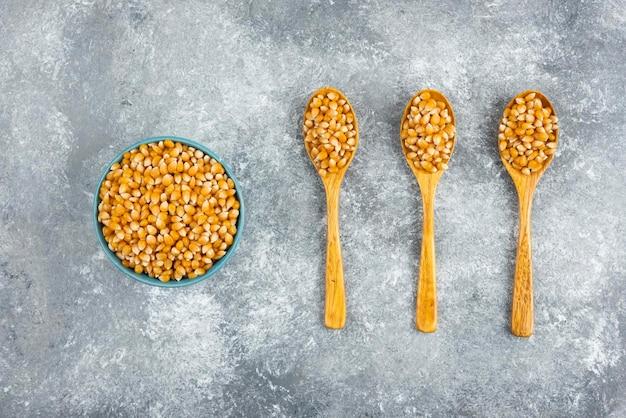 Miska ziaren kukurydzy na marmurowym stole.