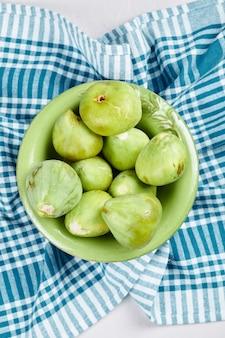 Miska zielonych fig na niebieskim obrusie.