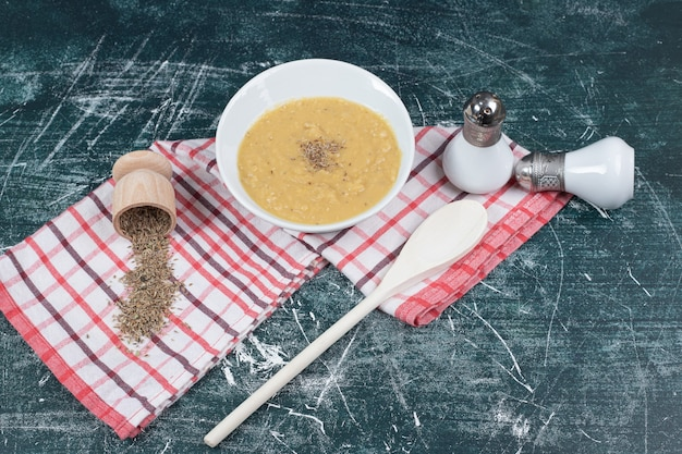 Miska zupa z soczewicy, sól, przyprawy i obrus na tle marmuru. wysokiej jakości zdjęcie