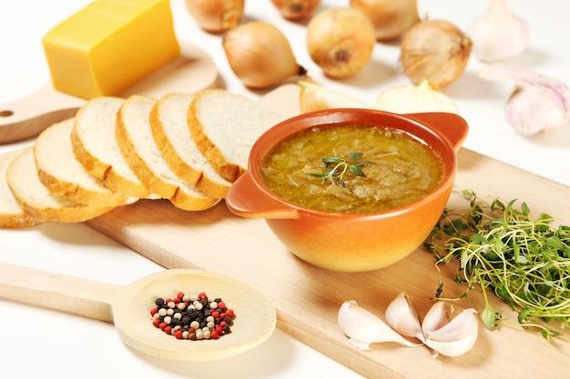 Miska zupy cebulowej i jej składników na białym stole