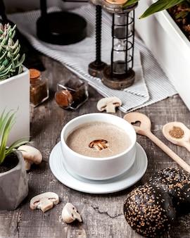 Miska zupy grzybowej podana z bułeczkami z czarnego chleba
