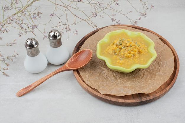 Miska zupy na drewnianym talerzu z solą i drewnianą łyżką