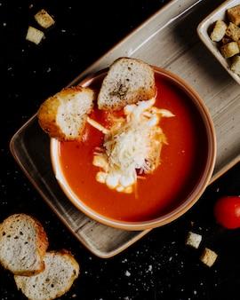 Miska zupy pomidorowej z posiekanym serem i krakersami w środku na tacy.