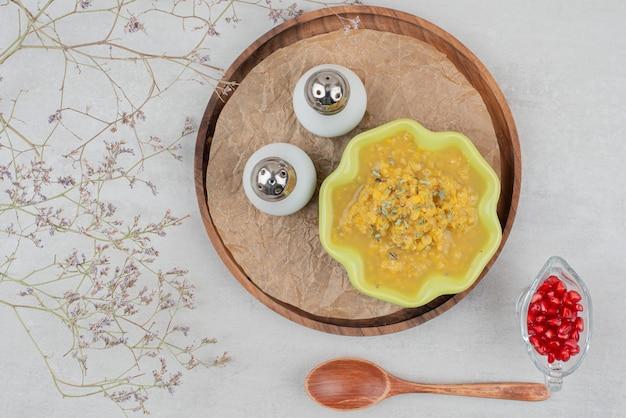 Miska zupy, soli i nasion granatu na białej powierzchni