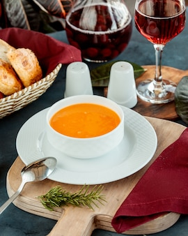 Miska zupy z soczewicy podawana z winem i chlebem