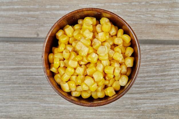 Miskę gotowanej kukurydzy na drewnianym stole.