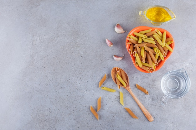 Miskę wielobarwnego surowego makaronu z olejem i szklankę wody.