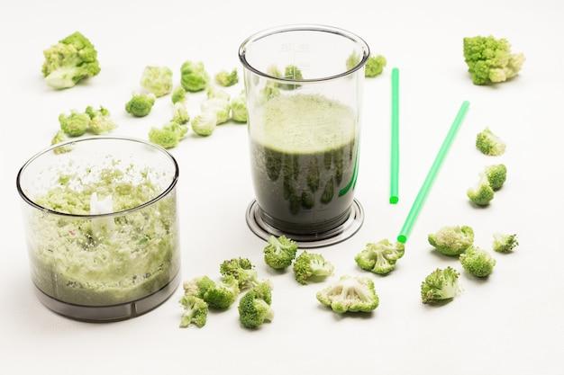 Miski blendera z zielonymi koktajlami warzywnymi.