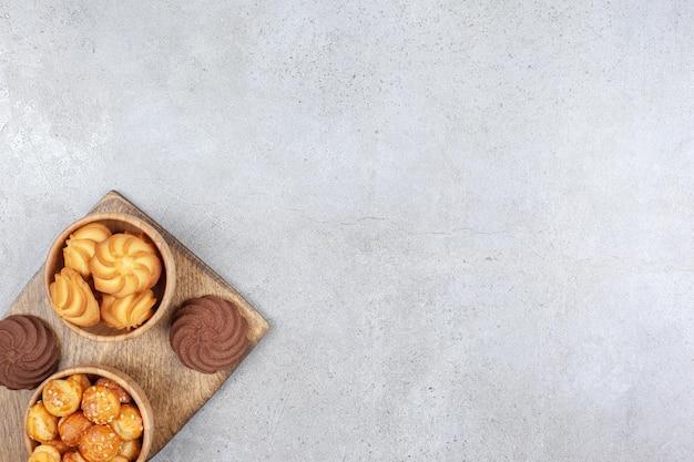 Miski ciasteczek obok brązowych ciasteczek na desce na tle marmuru. wysokiej jakości zdjęcie