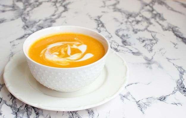 Miski dyniowej zupy na białym tle z szarym materiałem i plasterkami dyni piżmowej