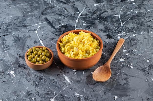 Miski gliniane z gotowanym ryżem i zielonym groszkiem na marmurowej powierzchni.