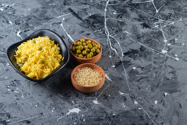 Miski gliniane z gotowanym ryżem i zielonym groszkiem na marmurowym tle.