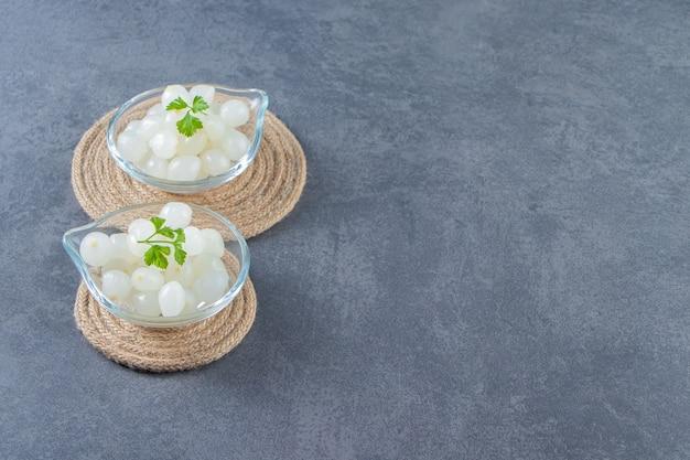 Miski marynowanej cebuli na trójnogu na marmurowej powierzchni