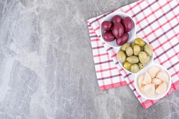 Miski marynowanych śliwek, oliwek i czosnku na obrusie.