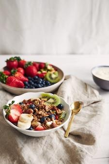 Miski muesli z jogurtem, owocami i jagodami na białej powierzchni